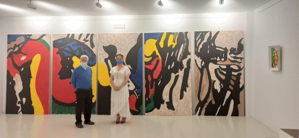 ambos artistas posando delante de la obra de Agüera